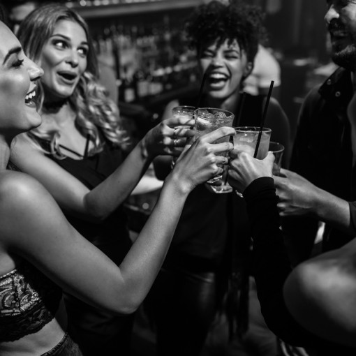 Group of friends partying in a nightclub and toasting drinks. Happy young people with cocktails at pub.